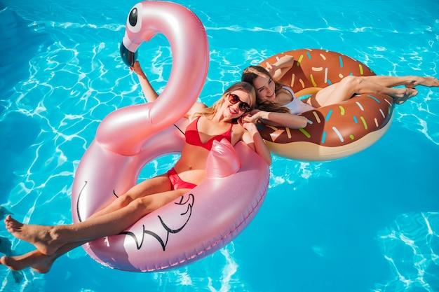 Vrouwen die zich in zwemmende ringen stellen