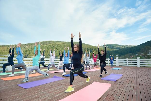Vrouwen die zich uitstrekken in lage longen poseren op yogamatten.