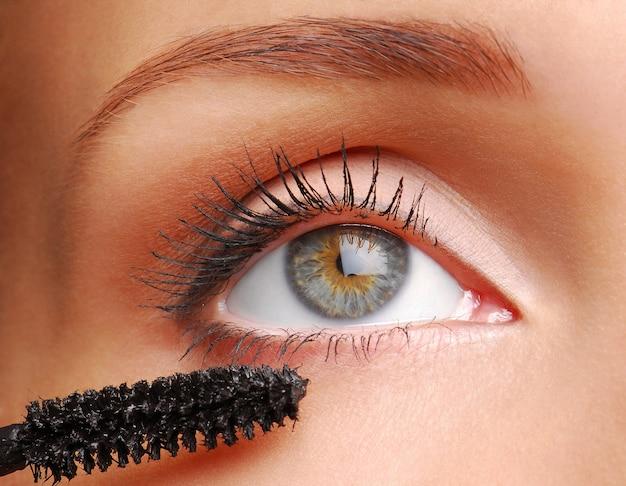 Vrouwen die zwarte mascara op de wimpers toepassen