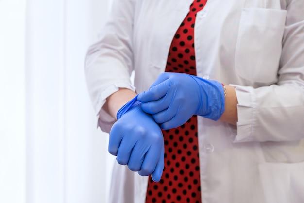 Vrouwen dienen rubberen handschoenen in met spuit met medicijn