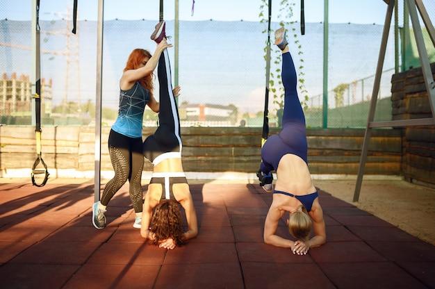 Vrouwen doen evenwichtsoefening met instructeur op sportveld buitenshuis, groepsfitnesstraining buiten