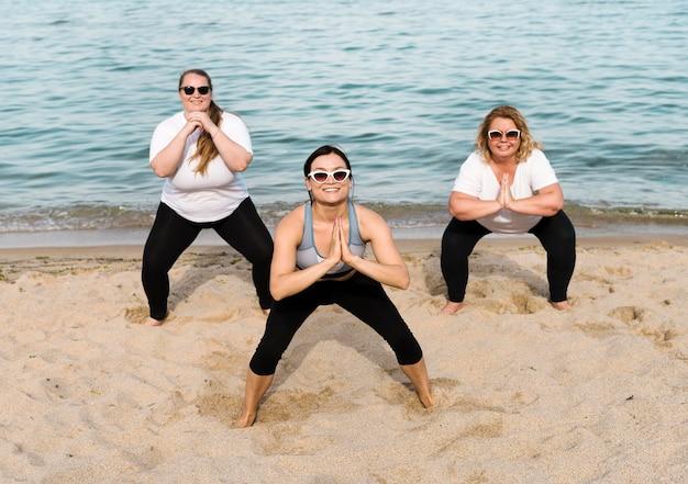 Vrouwen doen kraakpanden naast de zee