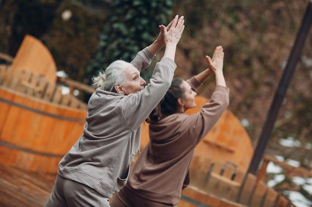 Vrouwen doen oefeningen sport en fitness buitenshuis. jonge en senior oudere vrouw warming-up en yoga bij glamping. moeder en dochter hebben zen zoals moderne fitnessvakantie.
