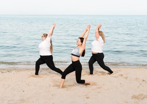 Vrouwen doen rekoefeningen naast de zee