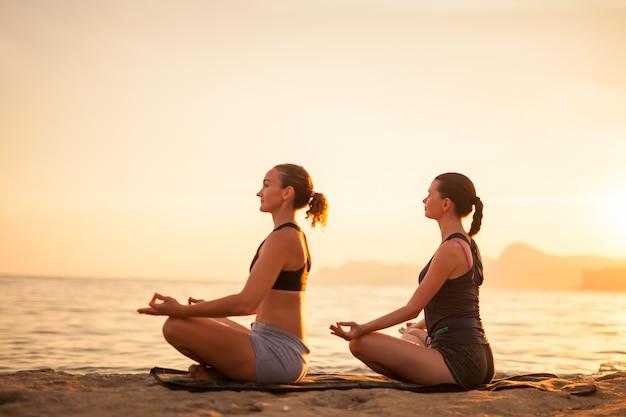 Vrouwen doen yoga op de natuur buiten bij zonsopgang