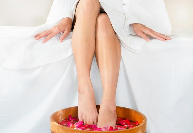 Vrouwen doorwekende voeten in houten kuuroordkom water met drijvende bloemen bij kuuroord.