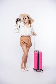 Vrouwen dragen hoeden, brillen, bagage en dragen camera's op weg naar hun reis