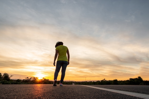 Vrouwen dragen jeans, sneakers en hoeden bij zonsondergang, staan langs de snelweg om te reizen