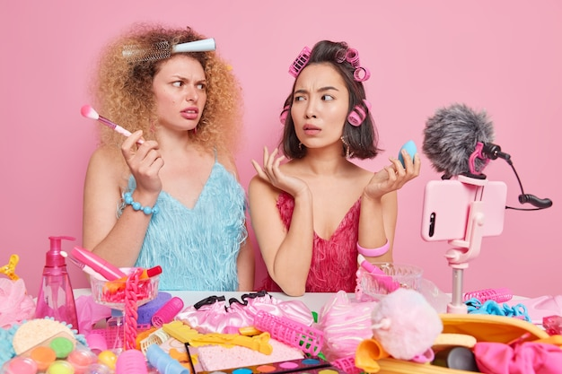 Vrouwen dragen jurk kijken elkaar verbaasd aan zitten aan tafel video opnemen voor beauty blog gebruik cosmetische producten gebruiken moderne smartphone geïsoleerd op roze