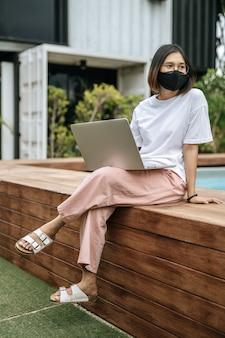 Vrouwen dragen maskers en spelen laptops bij het zwembad.