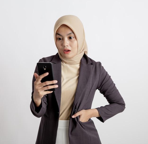 Vrouwen dragen pakken hijab verrast kijken naar de telefoon, formeel werk concept geïsoleerde witte achtergrond