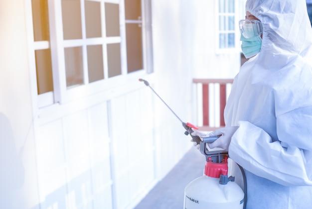 Vrouwen dragen persoonlijke beschermende pakken, bril, maskers en handschoenen die desinfectie en decontaminatie op een openbare plaats maken om de verspreiding van ziekten tijdens crisis covid-19 te verminderen.