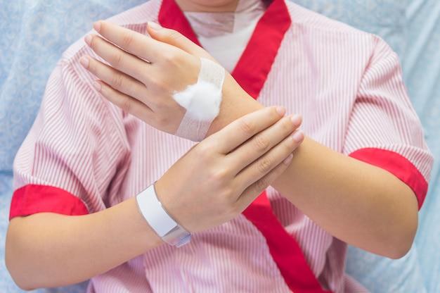 Vrouwen dragen rode patiënten polspijn en een watje op de rug van de hand.