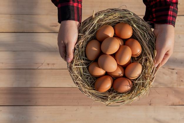 Vrouwen dragen rood gestreepte overhemden, leggen verse eieren in rotanmanden op houten vloer.