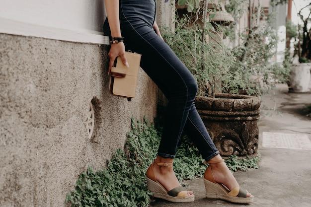 Vrouwen dragen sandalen of schoenen met een portemonnee, tas en tas