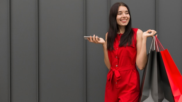 Vrouwen dragende zakken die de ruimte van het mobiele telefoonexemplaar houden