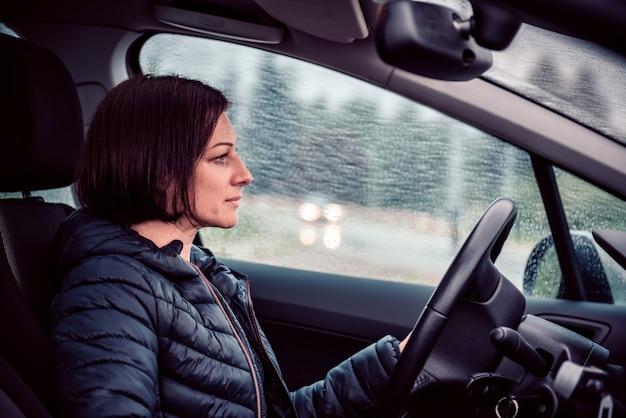 Vrouwen drijfauto op de autosnelweg in de regen