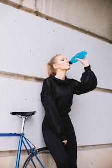 Vrouwen drinkwater dichtbij fiets