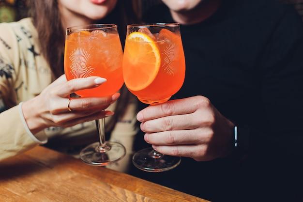 Vrouwen een glazen aperol spritz aan de eettafel.