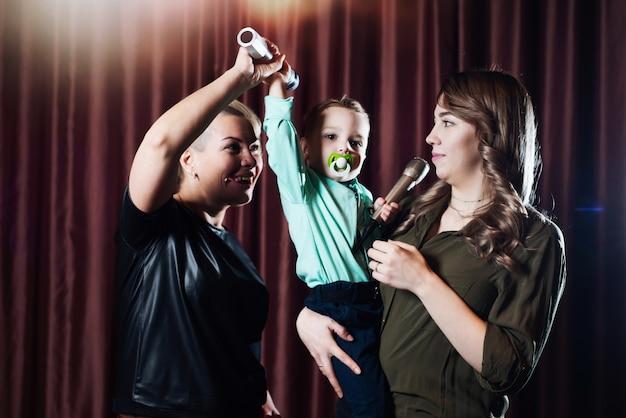 Vrouwen en een klein kind zingen op het podium in microfoons in karaoke