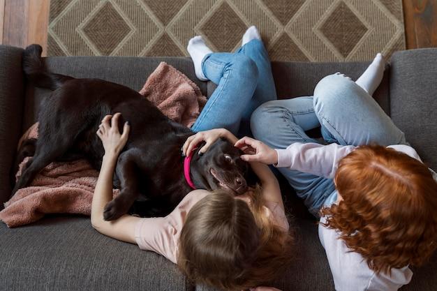 Vrouwen en hond die op bank leggen