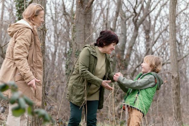 Vrouwen en jong geitje in bos middelgroot schot