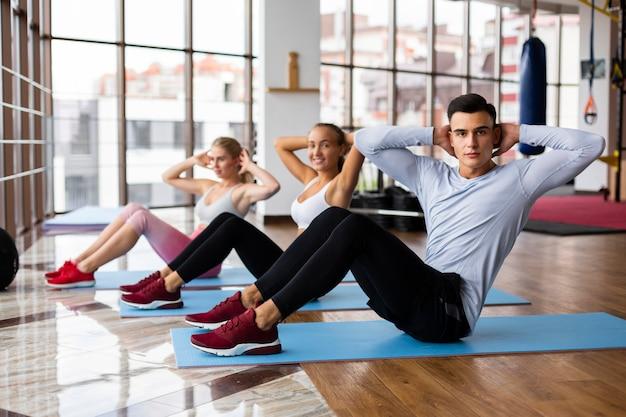 Vrouwen en man die bij gymnastiek uitoefenen