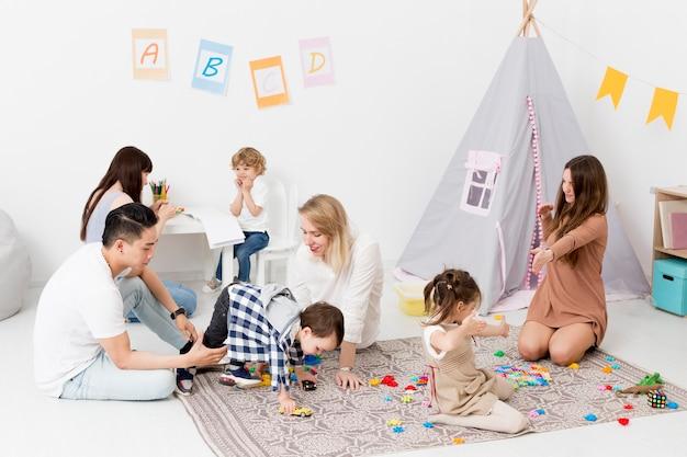 Vrouwen en man spelen met kinderen thuis