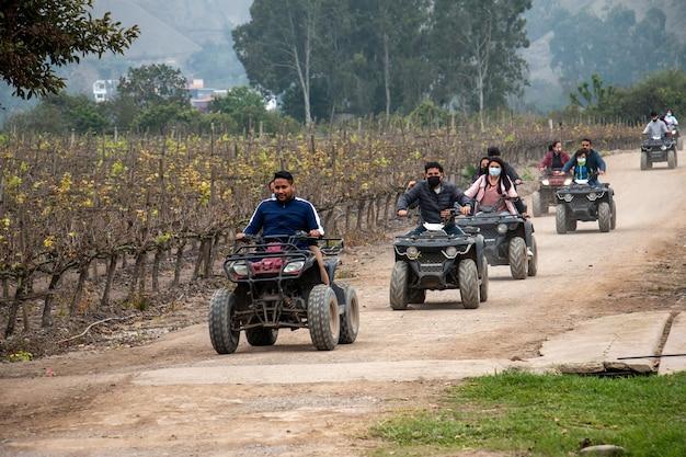 Vrouwen en mannen op atv's genieten van een ritje in een veld
