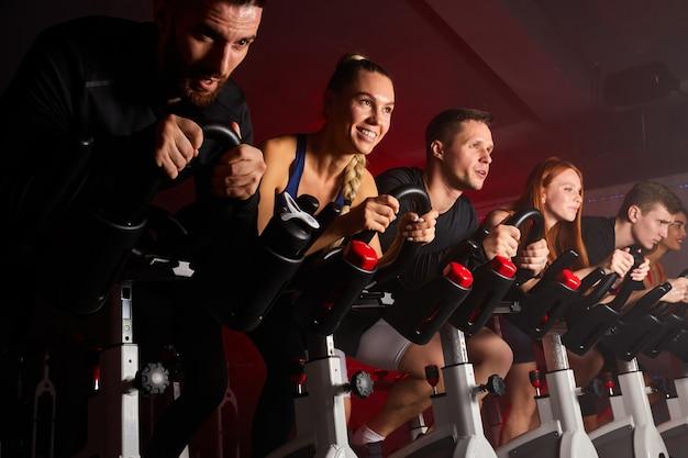 Vrouwen en mannen op fietsen machine trainen in de moderne sportschool kijken ernaar uit, zijaanzicht op mensen tijdens de training