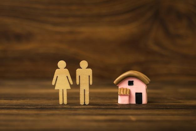 Vrouwen- en mannenfiguren van hout en een model van een huis op een houten fontein. het concept van huisvesting acquisitie.