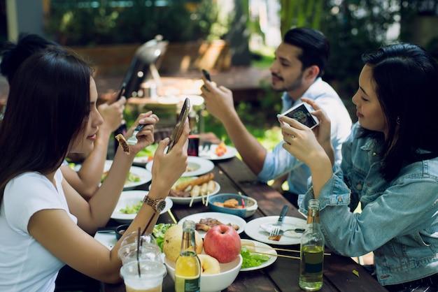 Vrouwen en vrienden gebruiken een telefoon tussen de maaltijden door