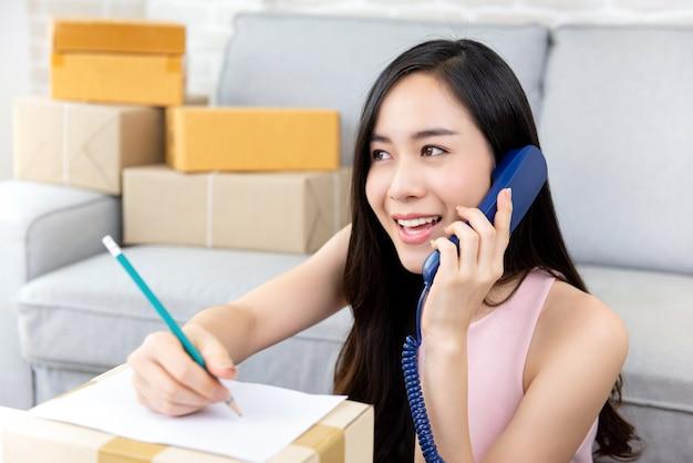 Vrouwen freelance online verkoper die orden van klant op de telefoon bevestigen