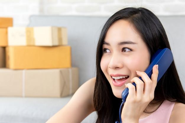 Vrouwen freelance verkoper die klant op de telefoon roepen om bevelen te bevestigen