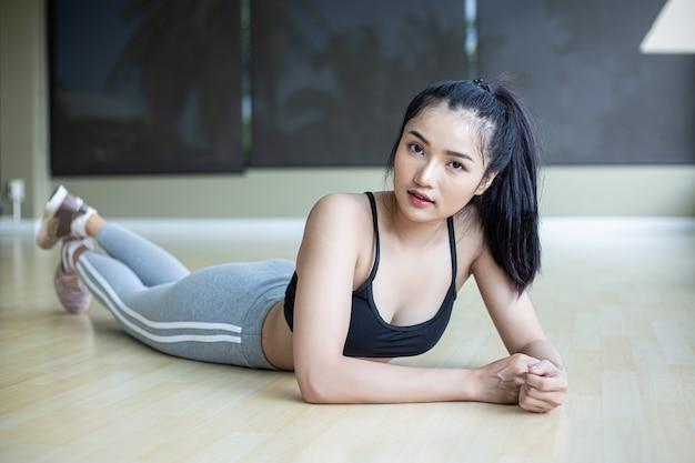 Vrouwen gaan liggen, ontspannen en heffen hun benen in de sportschool.