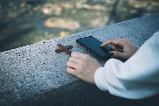 Vrouwen gebruiken een smartphone bij de hand met een kruis ernaast.