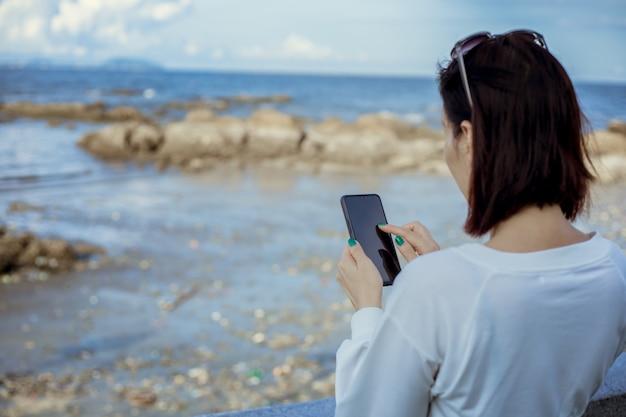 Vrouwen gebruiken smartphone bij de hand buiten.