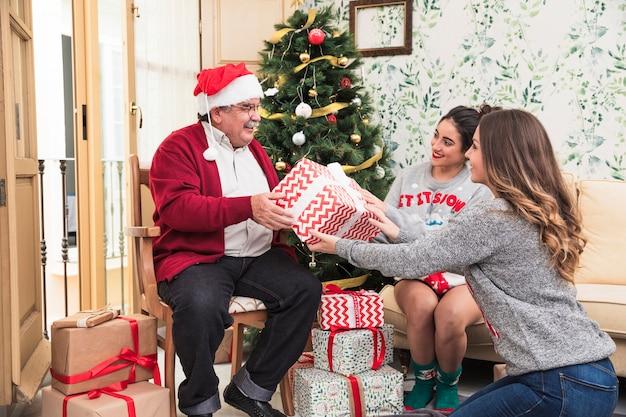 Vrouwen geven grote geschenkdoos aan de oude man