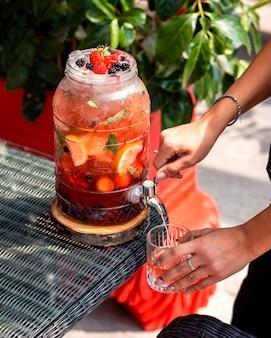 Vrouwen gietend fruitwater van glaskruik met kraan