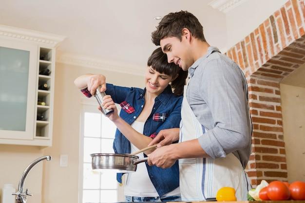Vrouwen gietend zout in werktuig terwijl man die een maaltijd in keuken voorbereiden