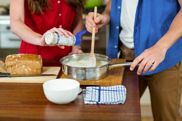 Vrouwen gietende melk terwijl man die het beslag in pan beweegt