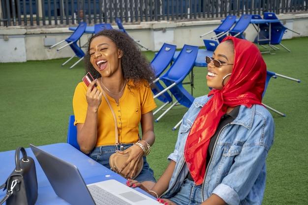 Vrouwen glimlachen en winkelen online terwijl ze in een café zitten