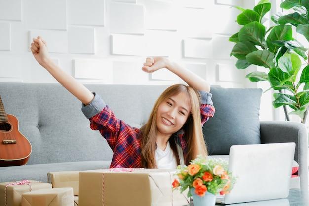 Vrouwen glimlachen gezicht met opgeheven arm met de doos met haar te leveren producten