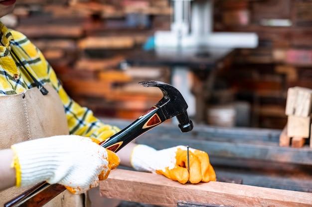 Vrouwen hameren spijkers in houten planken