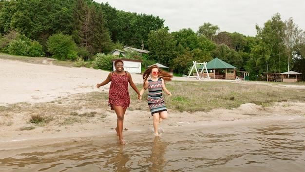 Vrouwen hand in hand en stappen in het water op het strand