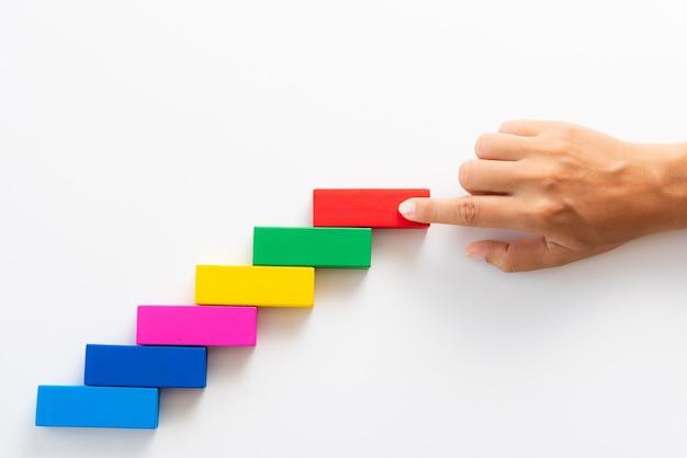 Vrouwen hand zetten rode houten blok op kleurrijke houten blokken in de vorm van een trap.