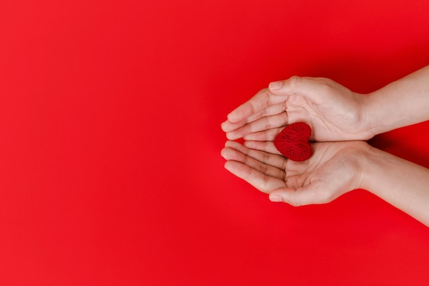 Vrouwen handen met rood hart op rood