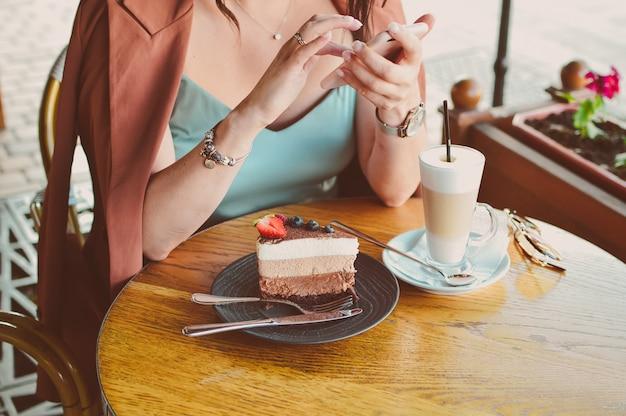 Vrouwen handen met telefoon en schrijft een bericht in een café