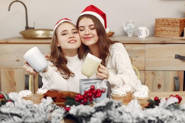 Vrouwen hebben cupcakes. vrienden in kerstversieringen. meisje in een kerstmuts.