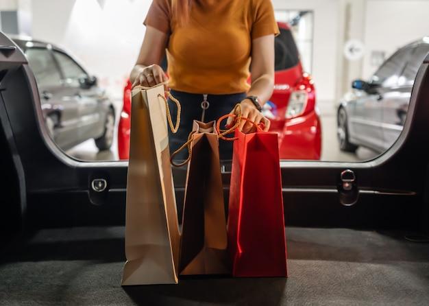 Vrouwen houden boodschappentassen in de auto